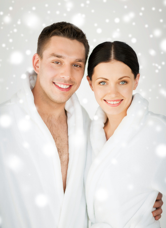 health and beauty concept - couple in spa salon in white bathrobes photo