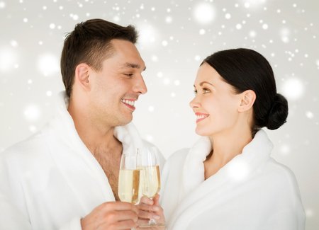 health and beauty, celebration, drinks concept - couple in spa salon in white bathrobes with champagne photo