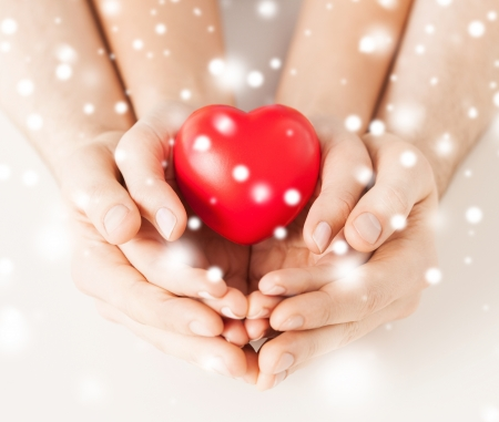 charity: family, charity, healthcare, health. christmas, x-mas and happy people concept - woman and man hands with heart Stock Photo
