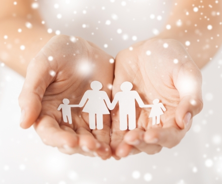big family: family, children, christmas, x-mas and happy people concept - woman cupped hands showing paper man family