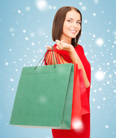 shopping, sale, gifts, christmas, x-mas concept - smiling woman in red dress with shopping bags photo