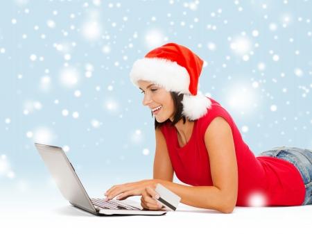 orden de compra: Navidad, Navidad, concepto de compras en línea - Mujer en el sombrero del ayudante de santa con el ordenador portátil y tarjeta de crédito