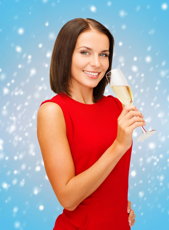 party, drinks, christmas, x-mas concept - smiling woman in red dress with a glass of champagne photo