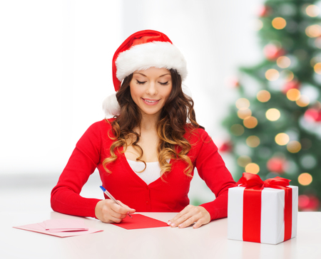 christmas, x-mas, gifts, presents, celebration concept - smiling woman in santa helper hat with gift box and postcard photo