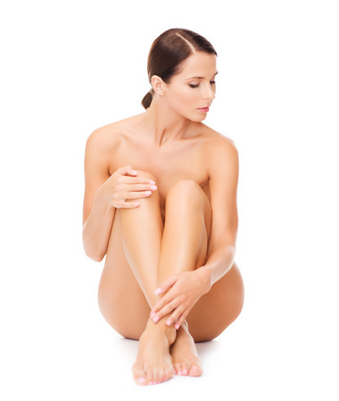 health and beauty concept - beautiful naked woman touching her legs photo
