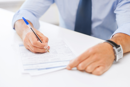 signing a contract: business, office, school and education concept - man signing a contract