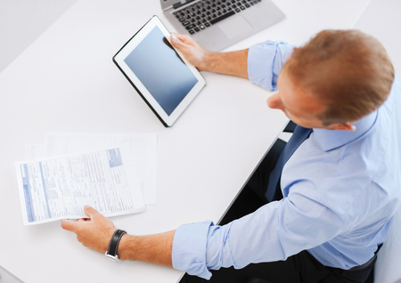 business, office, school and education concept - businessman with tablet pc and papers in office photo