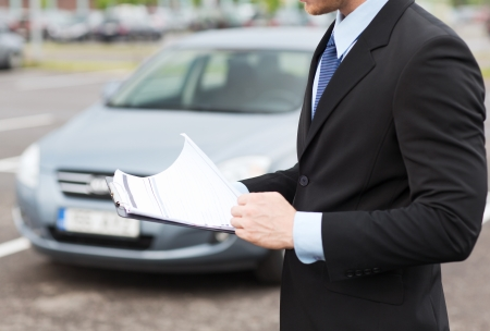 secondhand: transportation and ownership concept - man with car documents outside