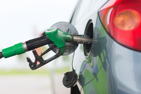 fueling: transportation and ownership concept - pumping gasoline fuel in car at gas station Stock Photo