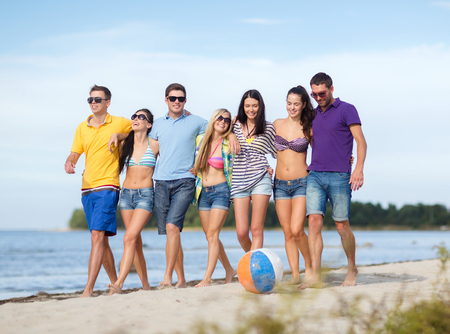 beach ball girl: summer, holidays, vacation, happy people concept - group of friends having fun with ball on the beach