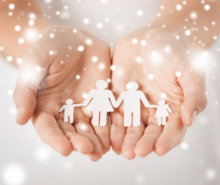 family, children, christmas, x-mas and happy people concept - woman cupped hands showing paper man family photo