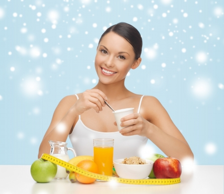 eating breakfast: food, nutrition, slimming, diet concept - young woman with healthy breakfast and measuring tape Stock Photo