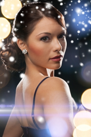 new years eve: luxury, vip, nightlife, party, christmas, x-mas, new years eve concept - beautiful woman in evening dress wearing diamond earrings