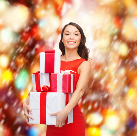 christmas, x-mas, valentines day, celebration concept - smiling woman in red dress with many gift boxes photo