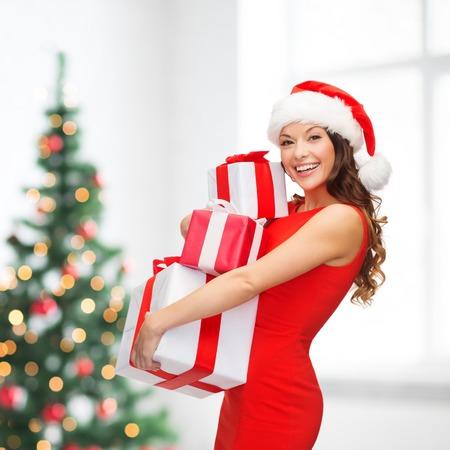 Vánoce, vánoce, zima, štěstí koncept - usmívající se žena v klobouku santa pomocník s mnoha dárkové krabičky