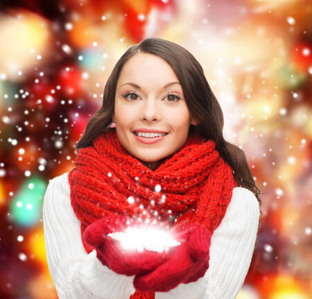 winter, people, happiness concept - woman in scarf and gloves with big snowflake photo