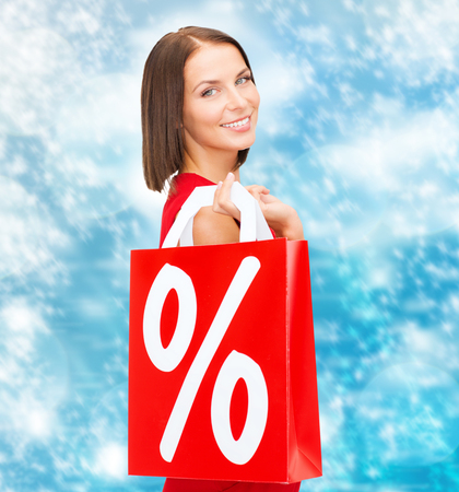 shopping, sale, gifts, christmas, x-mas concept - smiling woman in red dress with shopping bags and percent sign photo