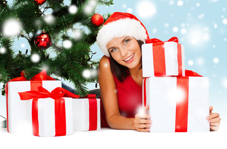 christmas, x-mas, winter, happiness concept - smiling woman in santa helper hat with many gift boxes and tree photo