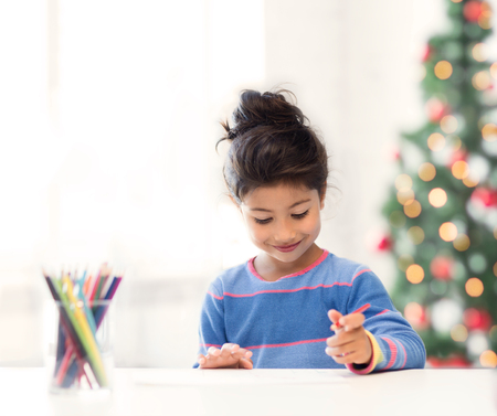 family, children, christmas, x-mas and happy people concept - little girl drawing Stock Photo - 23287727