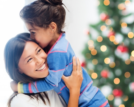 small tree: family, children, christmas, x-mas and happy people concept - hugging mother and daughter Stock Photo
