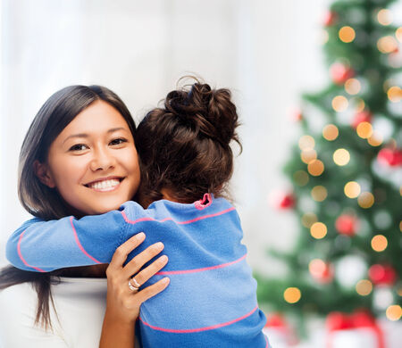 family, children, christmas, x-mas and happy people concept - hugging mother and daughter photo
