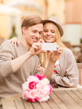 summer holidays, dating and technology concept - couple taking picture with smartphone at cafe in the city photo