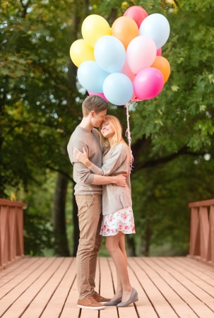 summer holidays, celebration and dating concept - couple with colorful balloons kissing in the park photo