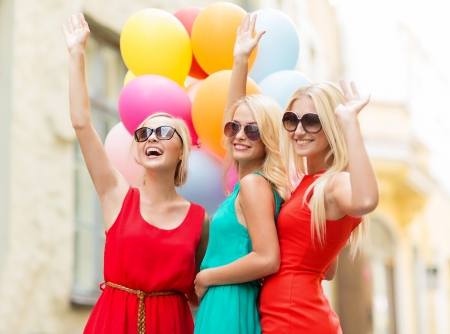 hen party: holidays and tourism, friends, hen party, blonde girls concept - three beautiful women with colorful balloons waving hands in the city Stock Photo