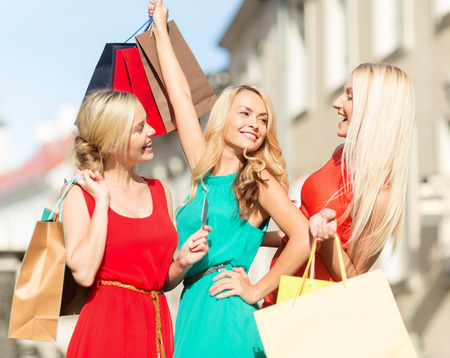 happy rich woman: sale and tourism, happy people concept - beautiful blonde women with shopping bags in the ctiy