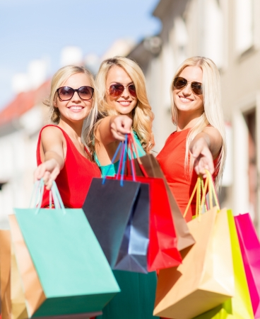 overspending: sale and tourism, happy people concept - beautiful blonde women with shopping bags in the ctiy