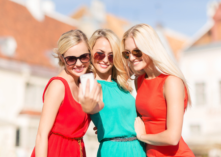 street party: holidays and tourism, modern technology concept - beautiful girls taking picture in the city