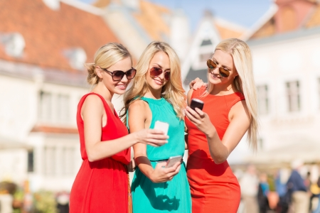 holidays and tourism, modern technology concept - beautiful blonde girls with smartphones in the city photo