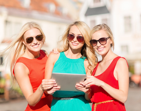 holidays and tourism concept - beautiful blonde girls toursits looking into tablet pc in the city photo
