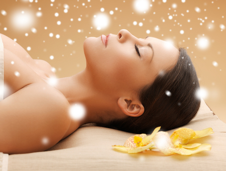relax skin: health and beauty concept - woman in spa salon lying on the massage desk