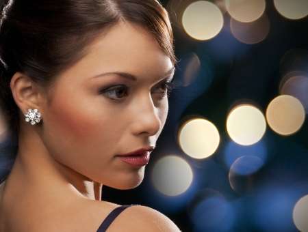 luxury, vip, nightlife, party concept - beautiful woman in evening dress wearing diamond earrings