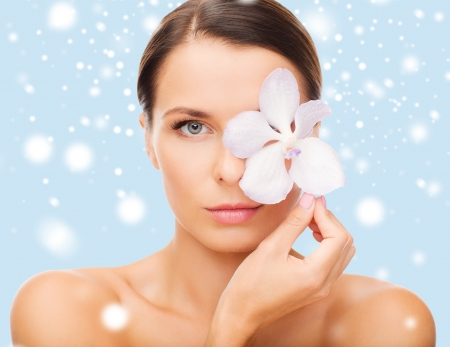 health and beauty concept - relaxed woman with orchid flower over eye photo