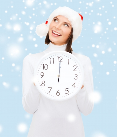 christmas, x-mas, winter, happiness concept - smiling woman in santa helper hat with clock showing 12 Stock Photo - 23288183