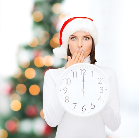 christmas, x-mas, winter, happiness concept - smiling woman in santa helper hat with clock showing 12 Stock Photo - 23288188
