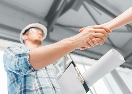 builder: architecture and home renovation concept - builder with blueprint shaking partner hand