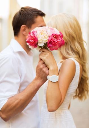 zomervakantie, liefde, relatie en dating concept - paar met een boeket bloemen in de stad