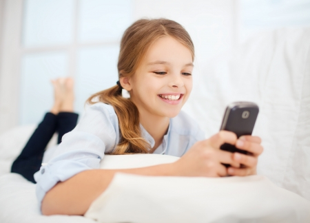 education, school, technology and internet concept - little student girl with smartphone at home photo