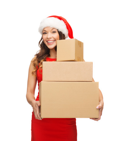 christmas, x-mas, winter, happiness concept - smiling woman in santa helper hat with many parcel boxes photo