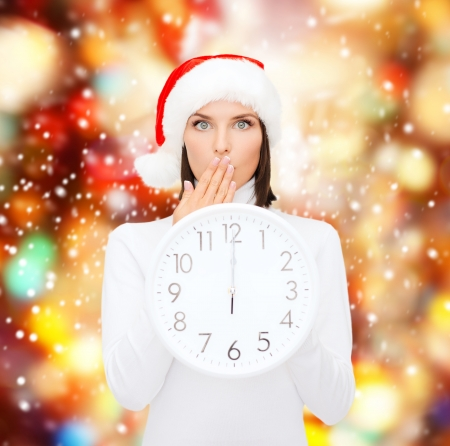 christmas, x-mas, winter, happiness concept - smiling woman in santa helper hat with clock showing 12 photo