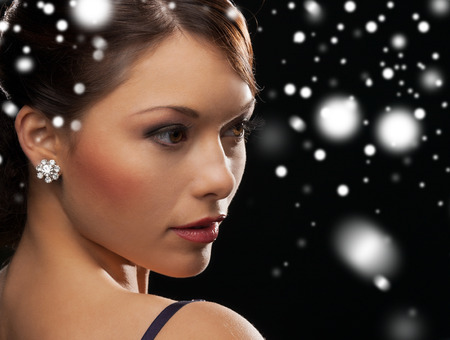 evening: luxury, vip, nightlife, party, christmas, x-mas, new years eve concept - beautiful woman in evening dress wearing diamond earrings