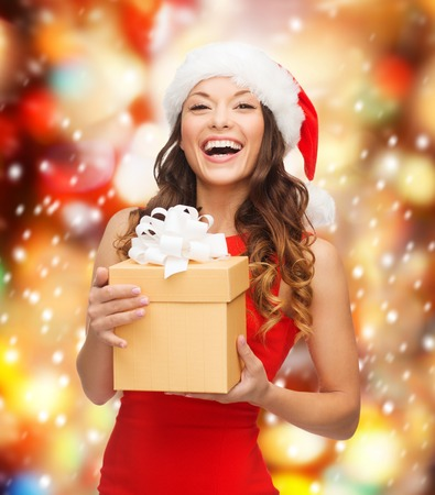 christmas, x-mas, new year, winter, happiness concept - smiling woman in santa helper hat with gift box photo