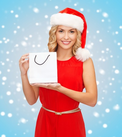 santa helper: shopping, sale, gifts, christmas, x-mas concept - smiling woman in red dress and santa helper hat with shopping bag Stock Photo