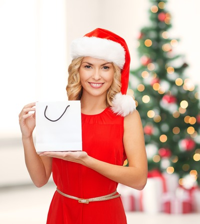 shopping, sale, gifts, christmas, x-mas concept - smiling woman in red dress and santa helper hat with shopping bag photo