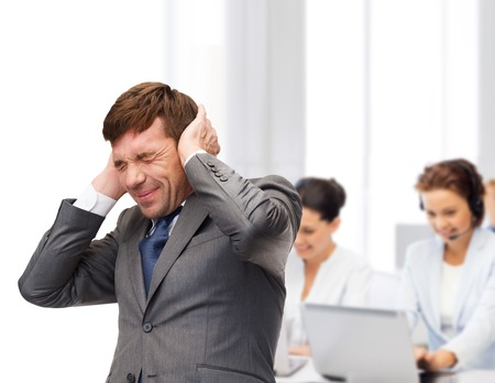 noise: business and office, stress, problem, crisis, loud noise concept - stressed buisnessman or teacher closing ears
