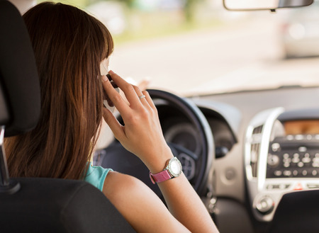 female driver: transportation and vehicle concept - woman using phone while driving the car