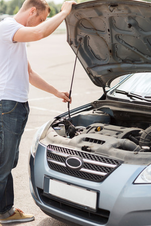 transportation and vehicle concept - man opening car bonnet and looking under hood photo